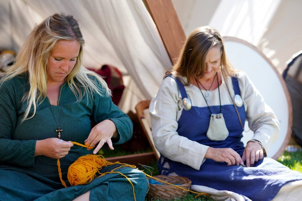 Two women demonstrating knitting at the viking camp