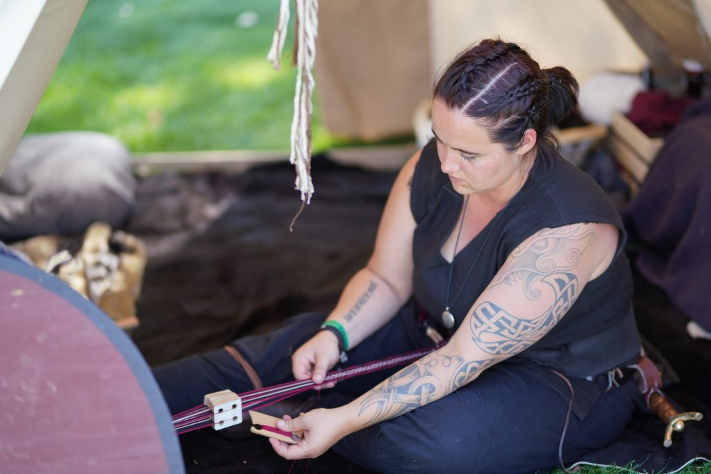 A woman weaving at the viking camp