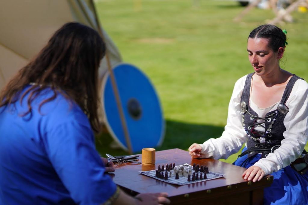 A man and a woman playing a viking board game