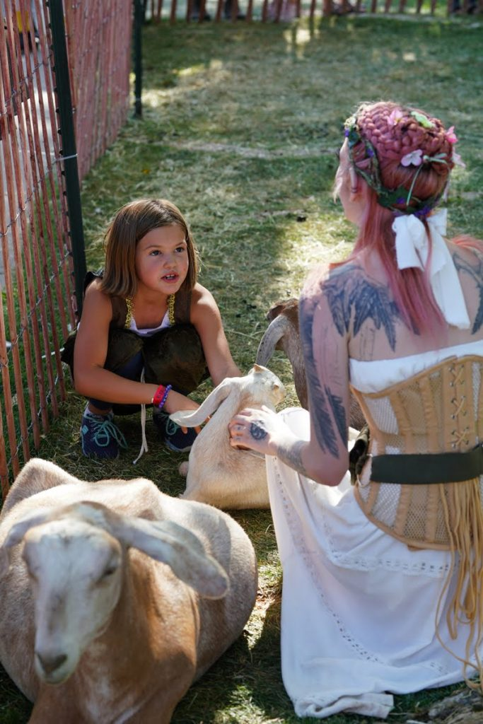 Girls petting goats at the Burr Family Farm petting zoo